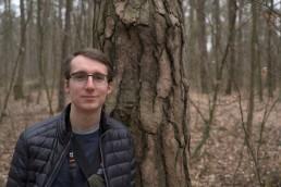 Portrait des Grafikdesigners Konrad Hauswald im herbstlichen Wald (Dresdener Heide). Er lehnt an einem Baum und schaut frontal in die Kamera.